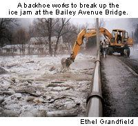 A backhoe works to break up the ice jam at the Bailey Avenue Bridge